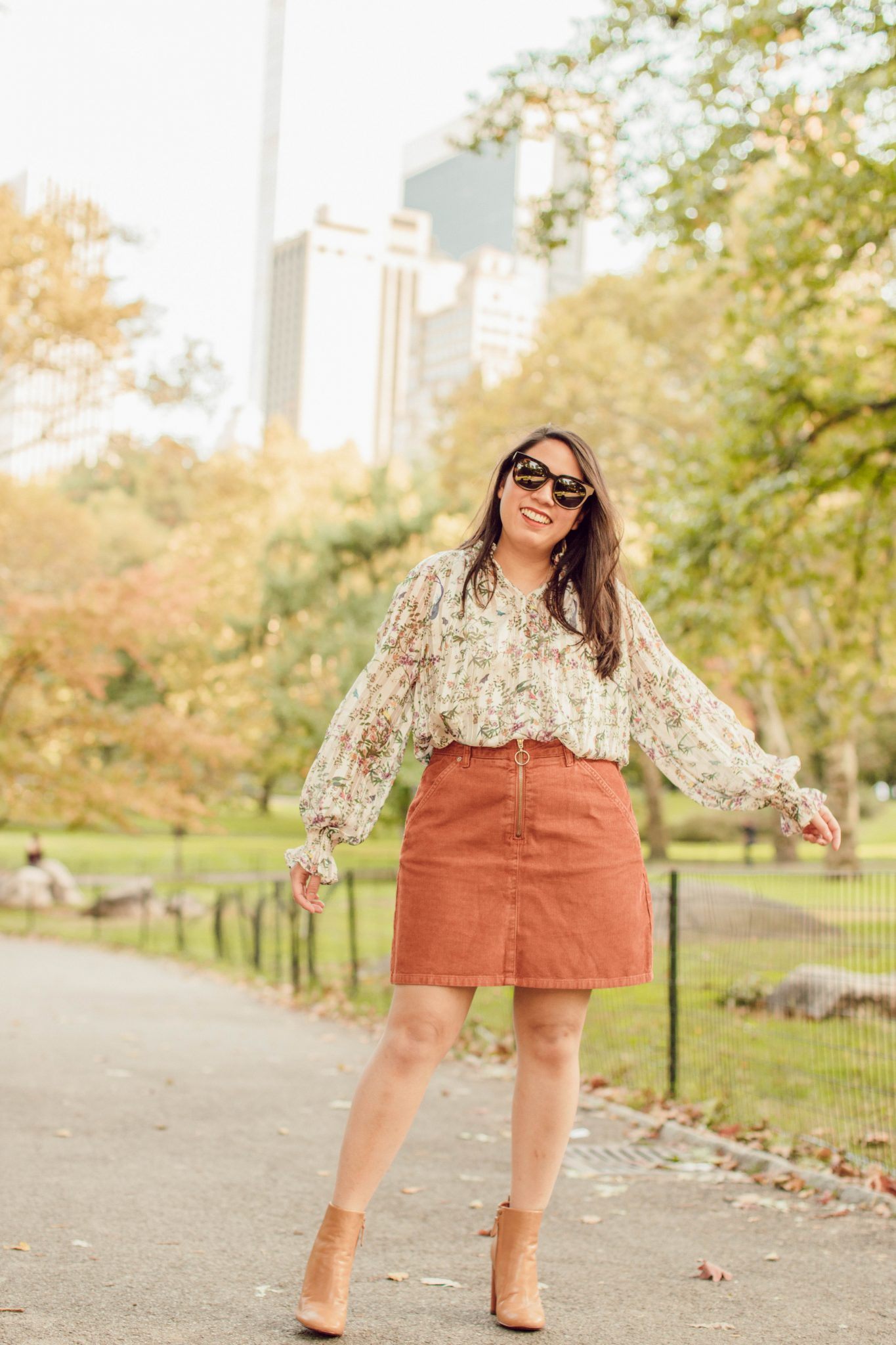 Things About Me featured by top US lifestyle blog Live Laugh Linda; Image of woman walking in a park wearing H&M blouse, Madewell mini skirt, Tory Burch booties and Gentle Monster sunnies.