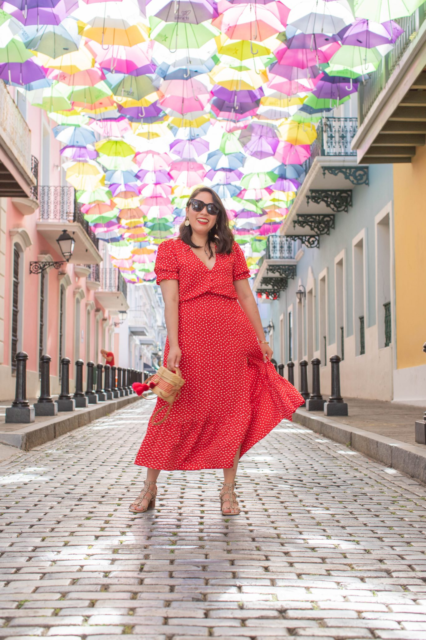 My New Outlook on Instagram... And no, I'm Not Complaining About The Instagram Algorithm by popular US influencer Live, Laugh, Linda: image of a woman standing on a cobble stone street with umbrellas hanging overhead In Puerto Rico and wearing a red Zara POLKA DOT DRESS WITH RUFFLE, Sole Society nude colored sandals with studs, Asos South Beach woven straw earrings, Shopbop Nannacay Baby Roge Pom Pom Bag, and Gentle Monster SALT 01 sunglasses.