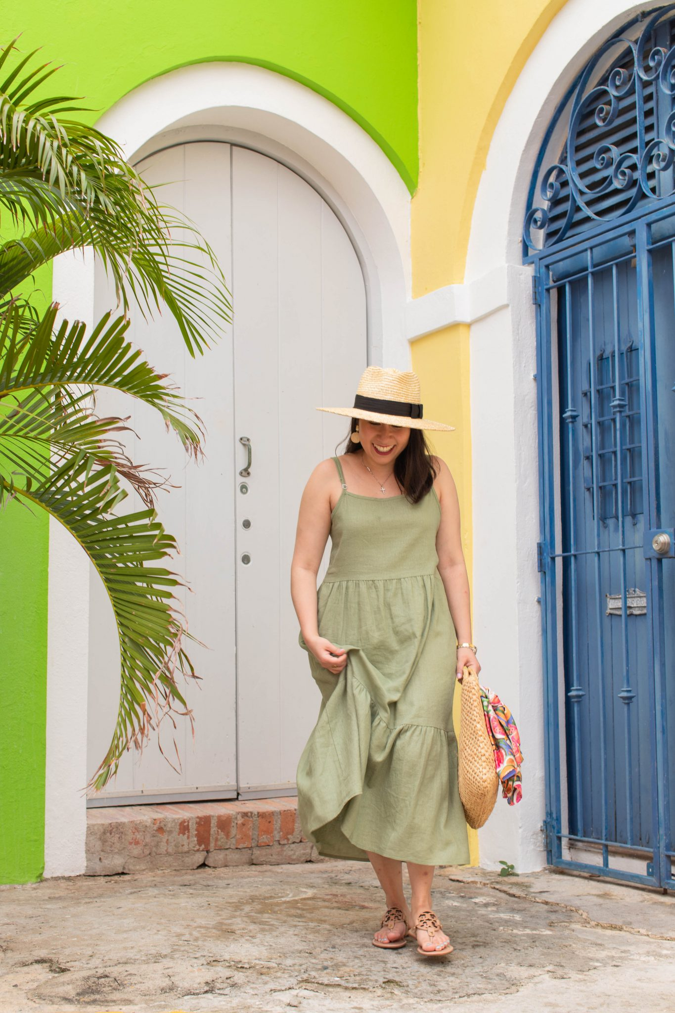 5 Essential Tips To Create Original Content And Grow Your Brand by popular New York influencer blog, Life Laugh Linda: image of a woman standing outside in front of a yellow and neon green building with a blue door and wearing a green maxi dress, brown sandals, straw sunhat, and holding a straw bag with a scarf tied on one of the handles.