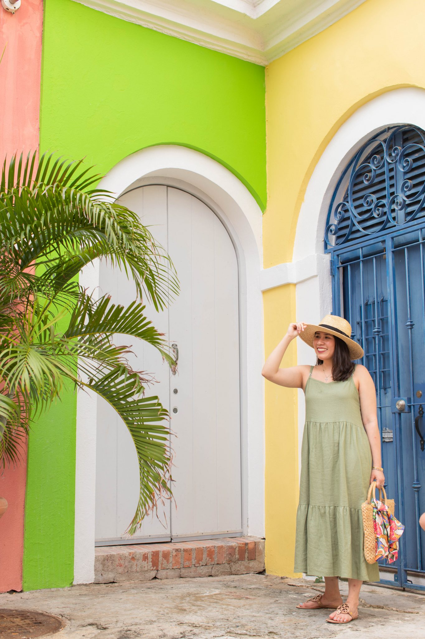 5 Essential Tips To Create Original Content And Grow Your Brand by popular New York influencer blog, Life Laugh Linda: image of a woman standing outside in front of a yellow, pink, and neon green building with a blue door and wearing a green maxi dress, brown sandals, straw sunhat, and holding a straw bag with a scarf tied on one of the handles.