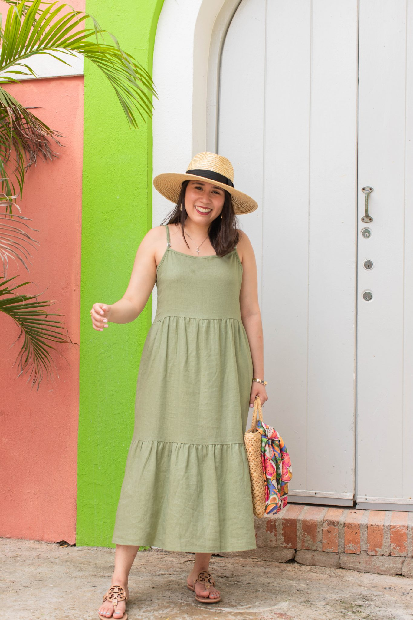 5 Essential Tips To Create Original Content And Grow Your Brand by popular New York influencer blog, Life Laugh Linda: image of a woman standing outside in front of pink and neon green building wearing a green maxi dress, brown sandals, straw sunhat, and holding a straw bag with a scarf tied on one of the handles.