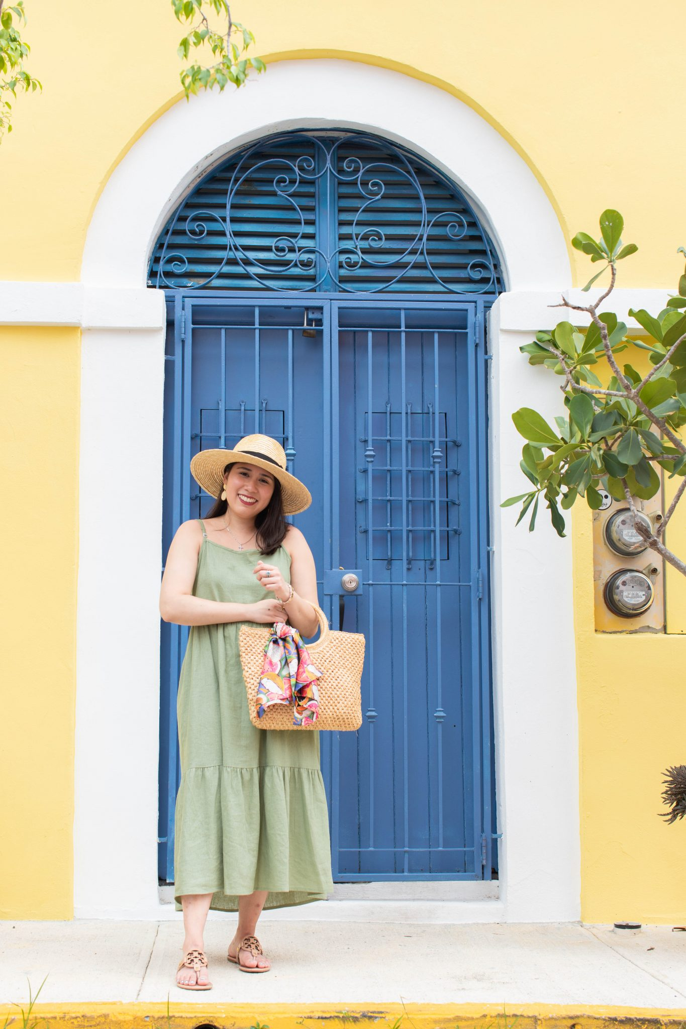 5 Essential Tips To Create Original Content And Grow Your Brand by popular New York influencer blog, Life Laugh Linda: image of a woman standing outside in front of a yellow building with a blue door and wearing a green maxi dress, brown sandals, straw sunhat, and holding a straw bag with a scarf tied on one of the handles.