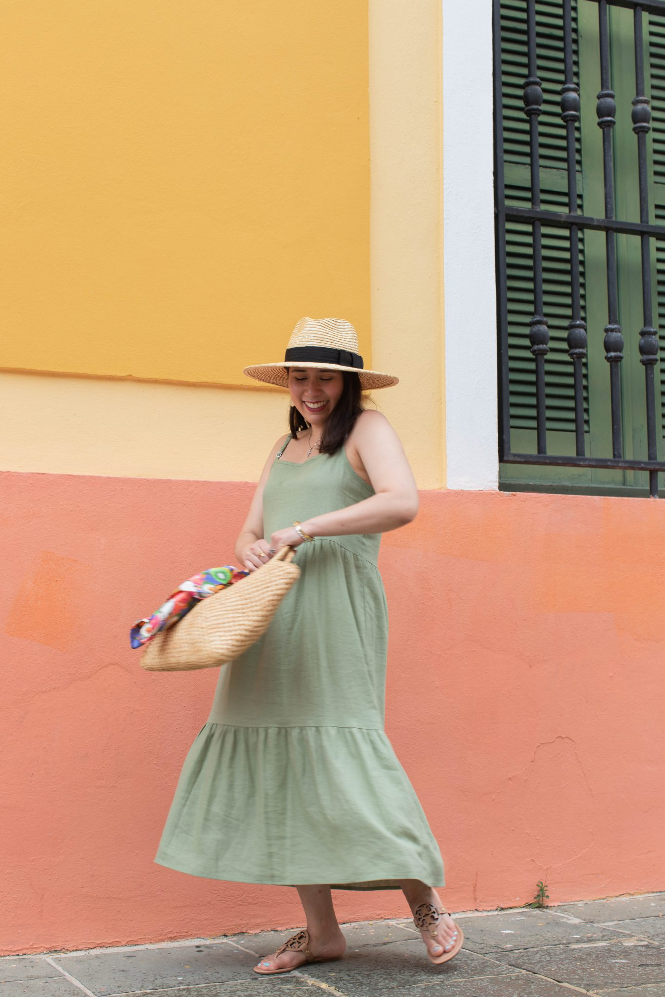 5 Essential Tips To Create Original Content And Grow Your Brand by popular New York influencer blog, Life Laugh Linda: image of a woman twirling outside in front of a yellow and orange building and wearing a green maxi dress, brown sandals, straw sunhat, and holding a straw bag with a scarf tied on one of the handles.