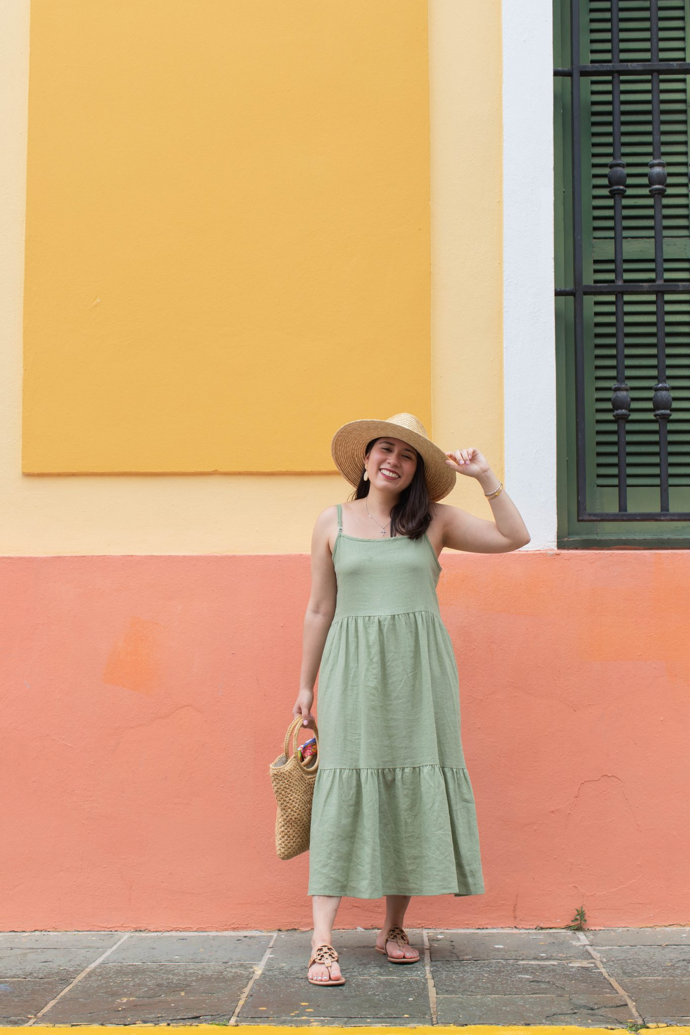 5 Essential Tips To Create Original Content And Grow Your Brand by popular New York influencer blog, Life Laugh Linda: image of a woman standing outside in front of a yellow and orange building and wearing a green maxi dress, brown sandals, straw sunhat, and holding a straw bag with a scarf tied on one of the handles.
