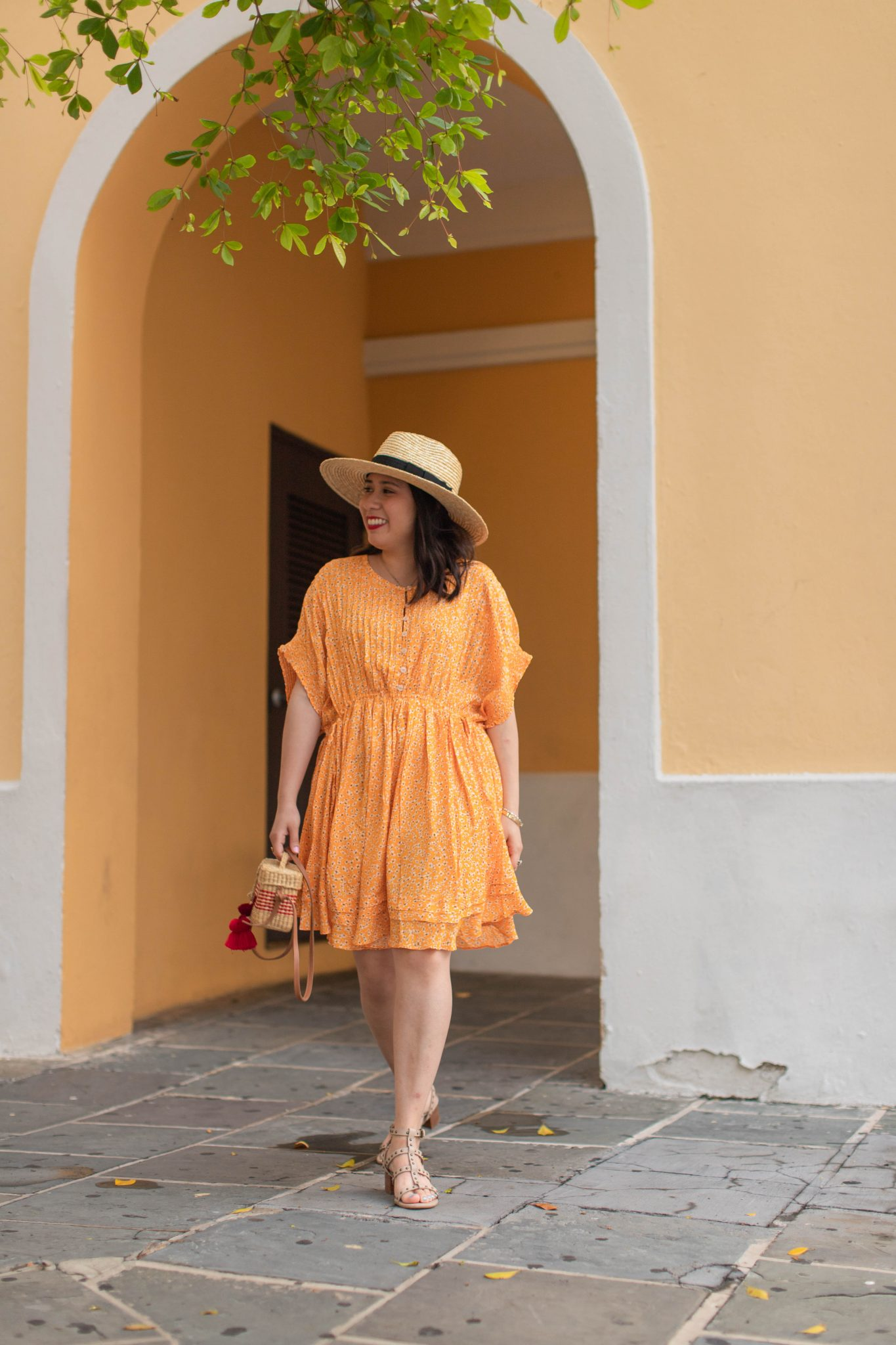 My 5 Personal Weekly Goals by popular New York life and style blog, Live Laugh Linda: image of a woman standing in front of a yellow building and wearing a Free People One Fine Day Mini Dress, ShopBop Nannacay Roge Small Crossbody Bag, Brixton Joanna Straw Hat and Sole Society shoes.