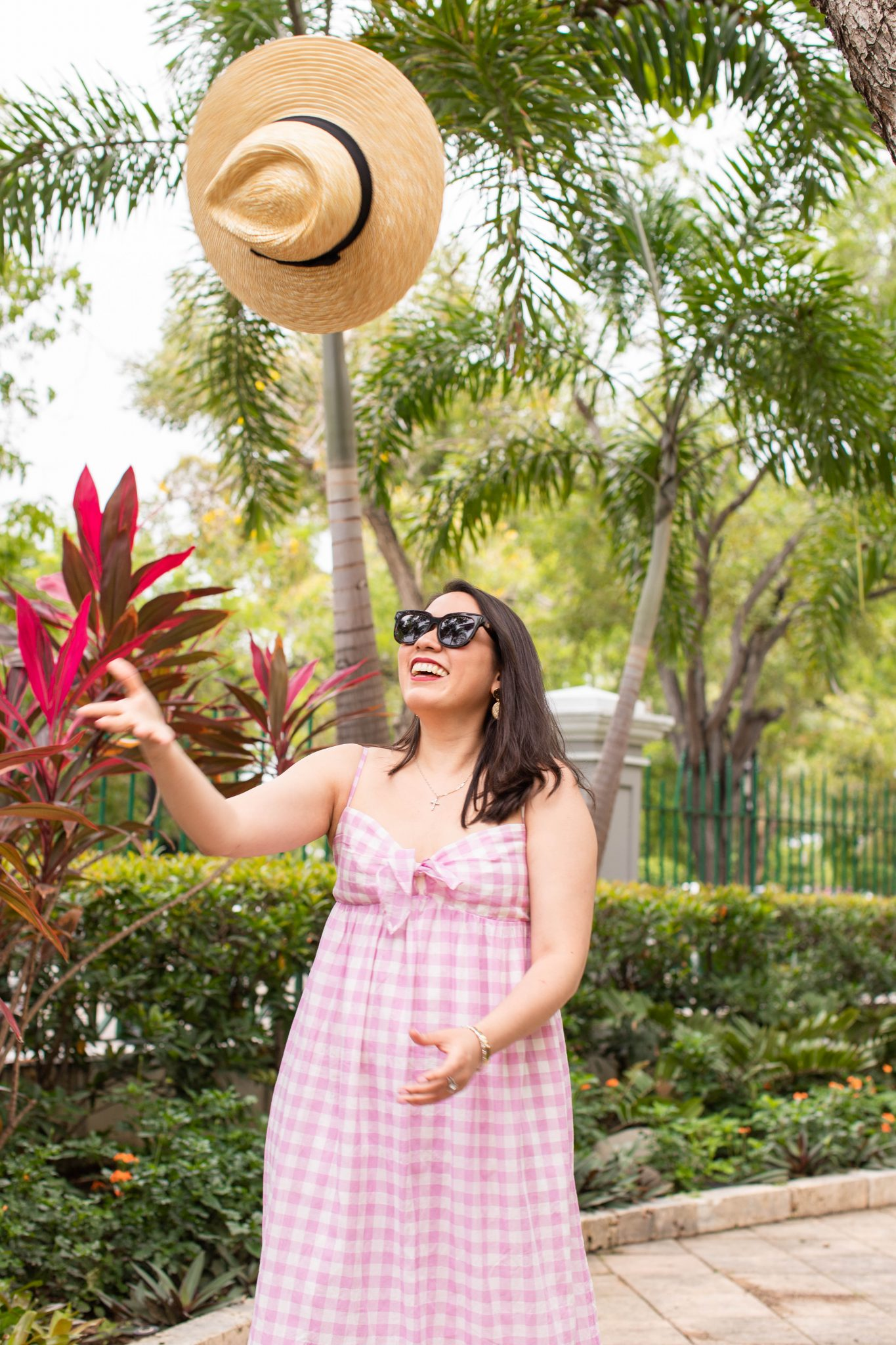 How to Grow Your Blog: What I Invest In & Is It Worth It? by popular New York life and style blog, Live Laugh Linda: image of a woman standing outside by some tropical plants and wearing a Beach dress with tie-front in oversized gingham, Saks Fifth Avenue Gentle Monster sunglasses, Nordstrom Brixton Joanna hat, and Tory Burch Miller Flip Flop.