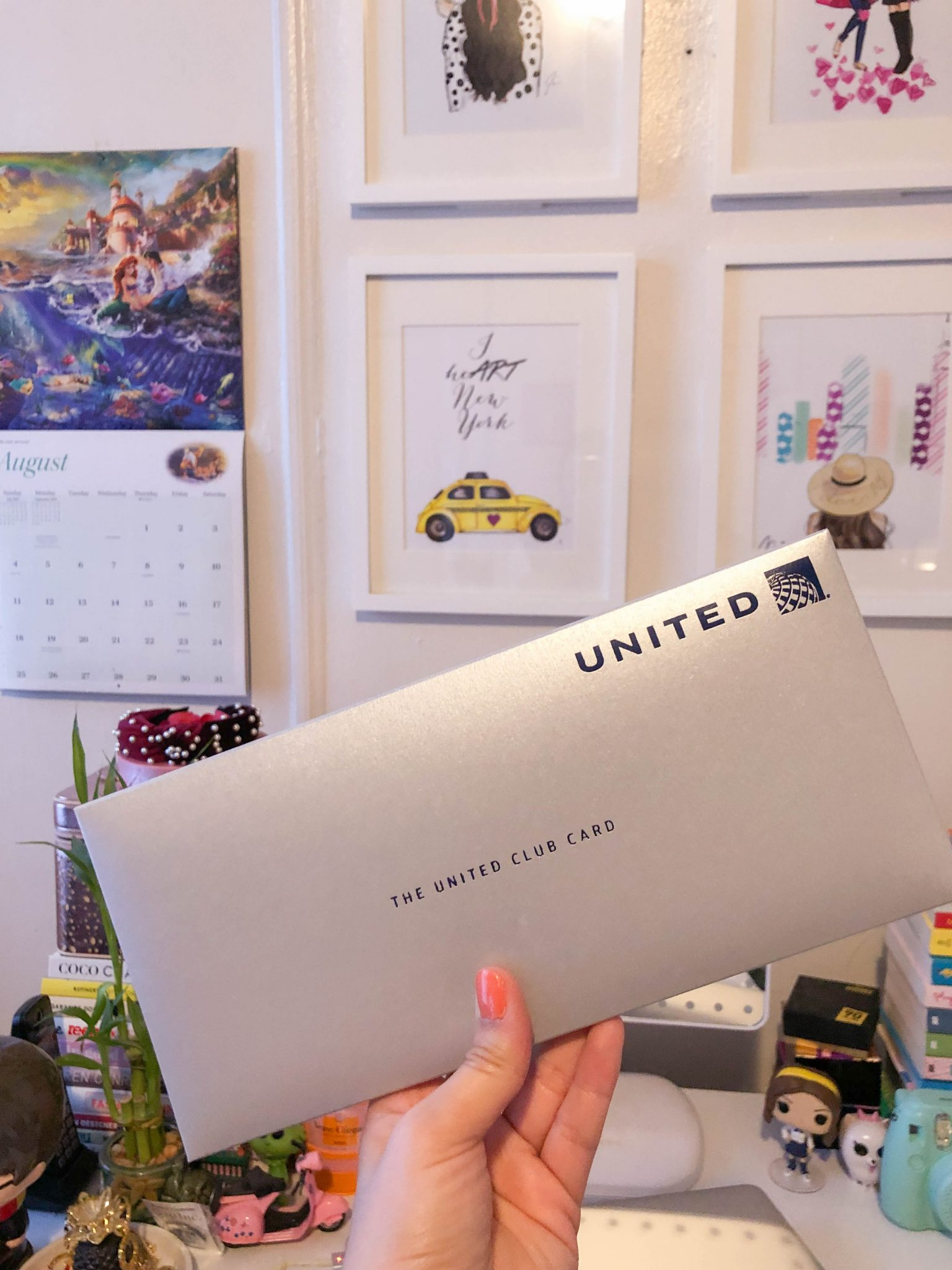 Week In Review :: A Friday Favorites Weekly Roundup by popular New York life and style blog, Live Laugh Linda: image of a woman holding a silver United Club Card envelope.