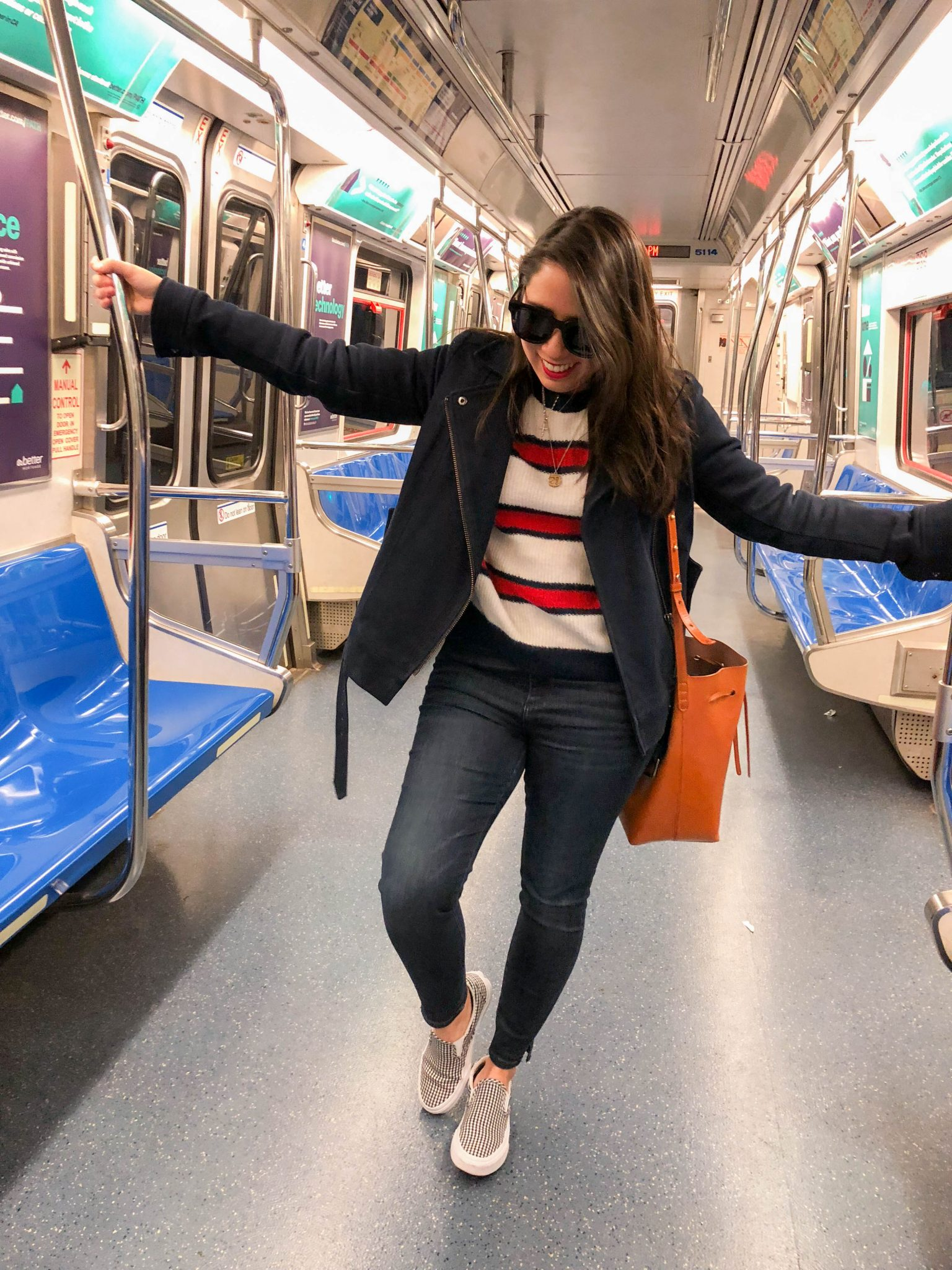 How to Step Out of Your Comfort Zone by popular New York life and style blog, Live Laugh Lind: image of a woman standing inside a subway train.