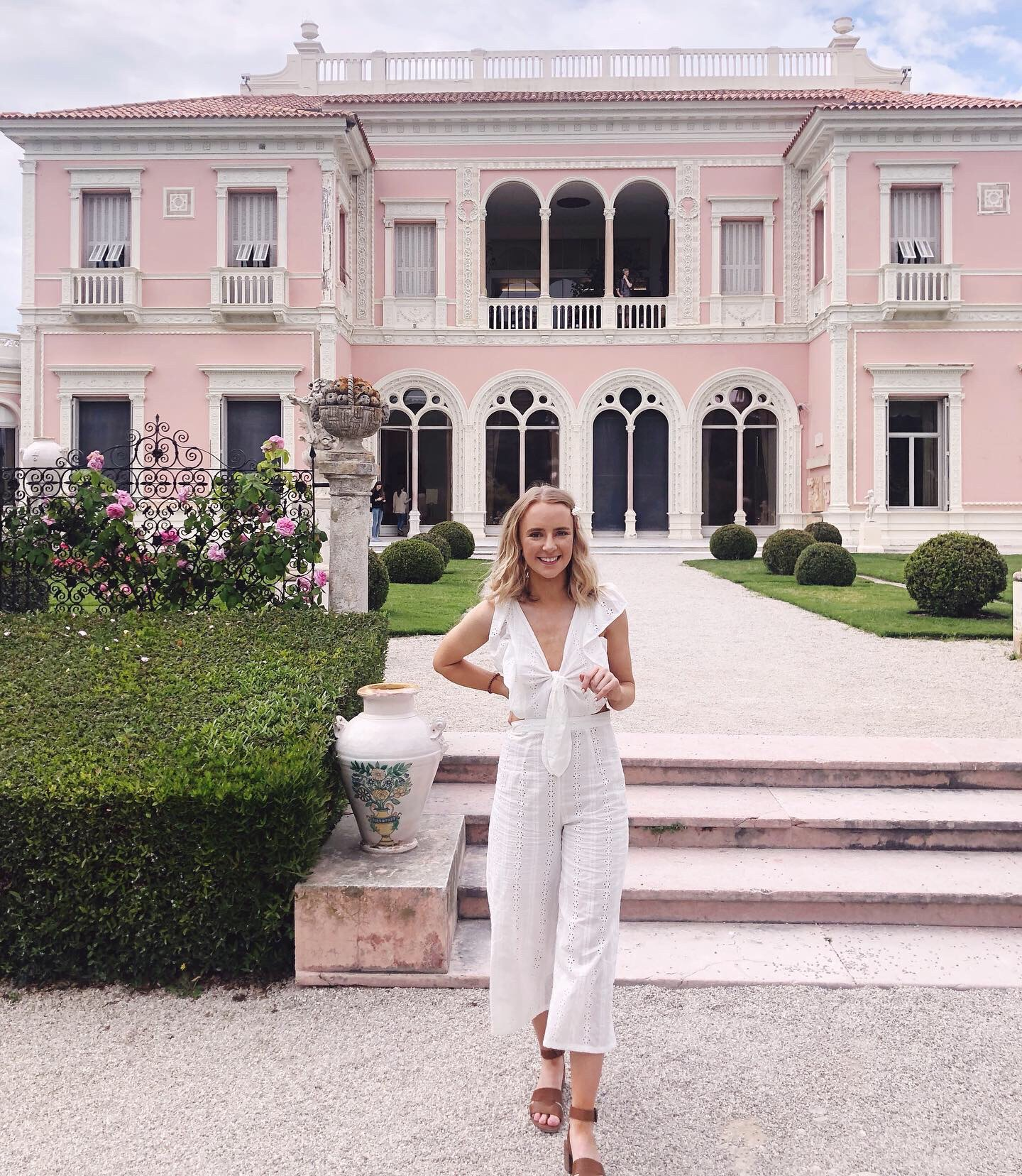Friends In New York City :: Meet Emma - Associate Publicist by popular New York lifestyle blog, Live Laugh Linda: image of a woman standing in front of a pink building and wearing a white eyelet jumpsuit.