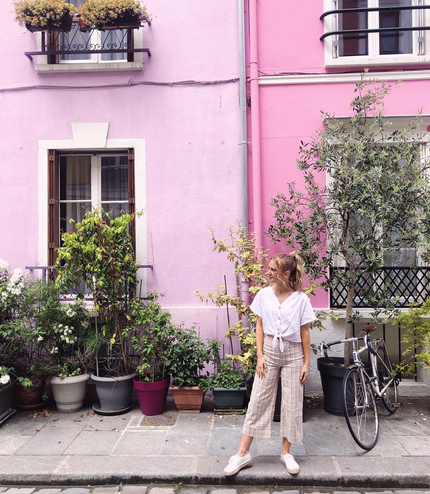 Friends In New York City :: Meet Emma - Associate Publicist by popular New York lifestyle blog, Live Laugh Linda: image of a woman standing in front of two pink buildings.