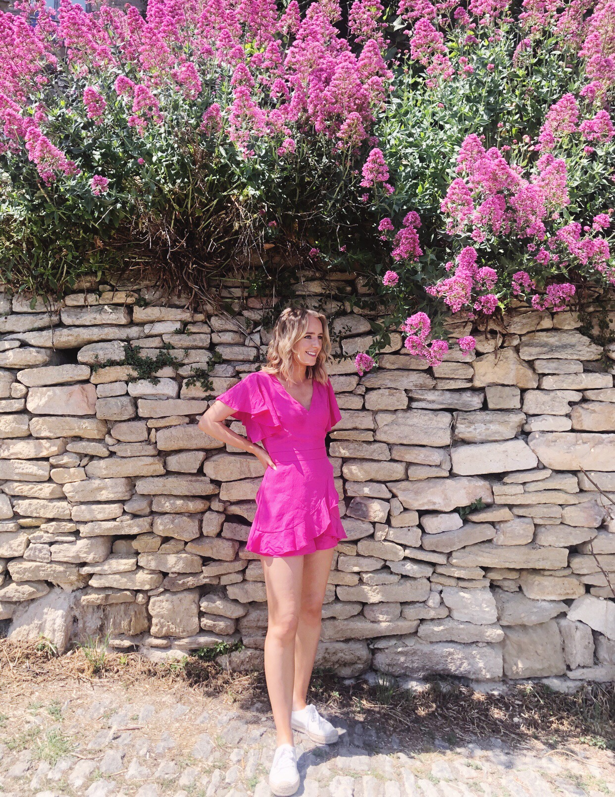 Friends In New York City :: Meet Emma - Associate Publicist by popular New York lifestyle blog, Live Laugh Linda: image of a woman wearing a pink ruffle dress and standing under some pink flowers.