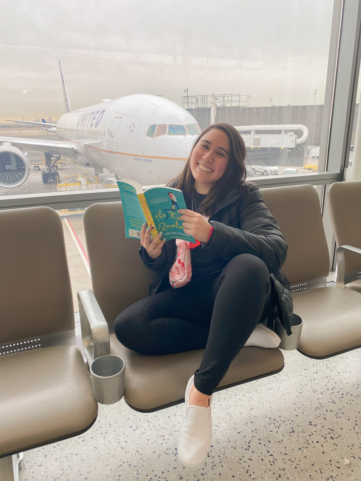 January Books by popular NYC life and style blog, Live Laugh Linda: image of a woman sitting in a airport and reading a book by Helen Hoang.