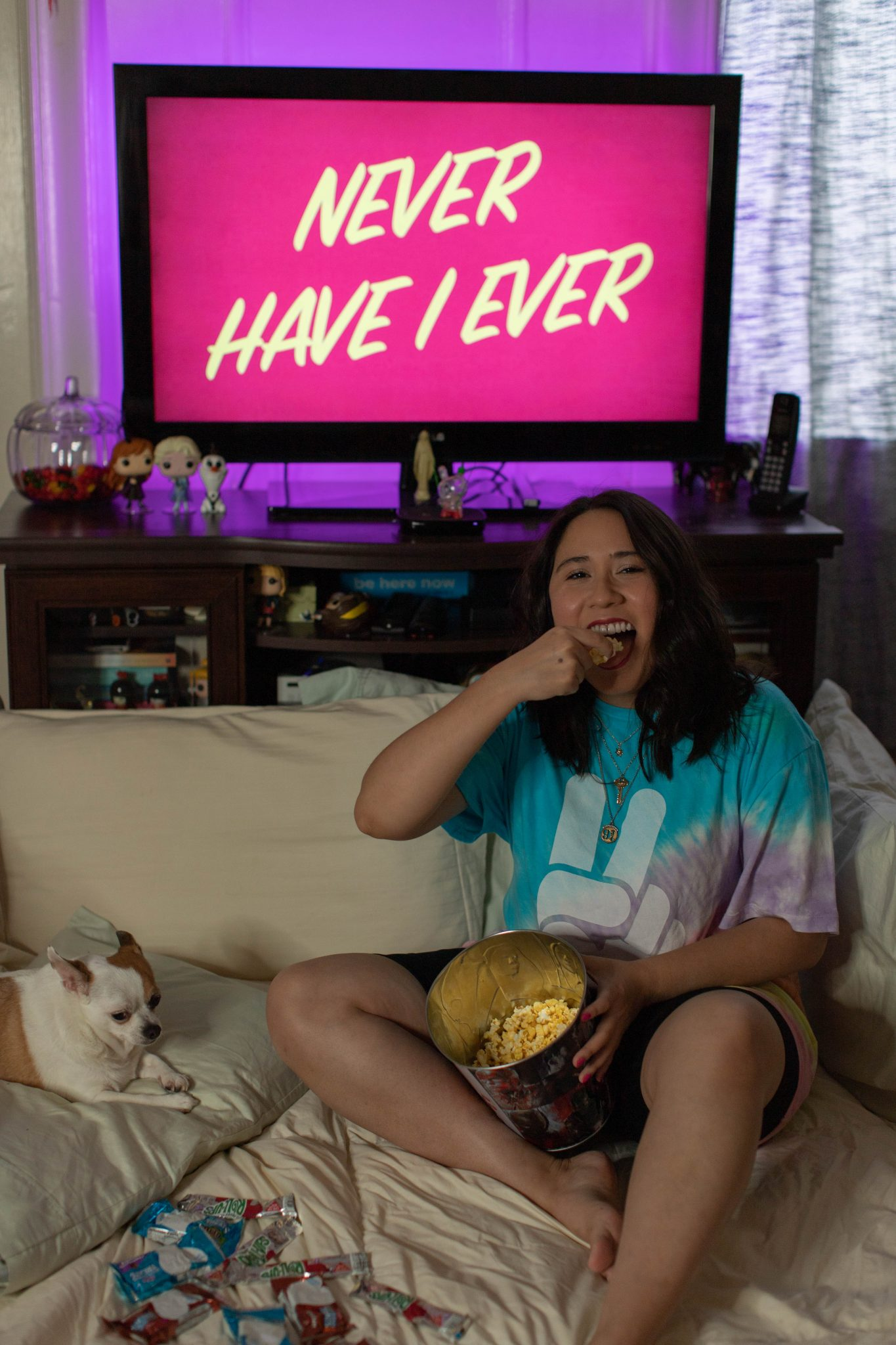 The best shows & movies to binge watch by popular NYC life and style blog, Live Laugh Linda: image of a woman watching Never Have I Ever on Netflix