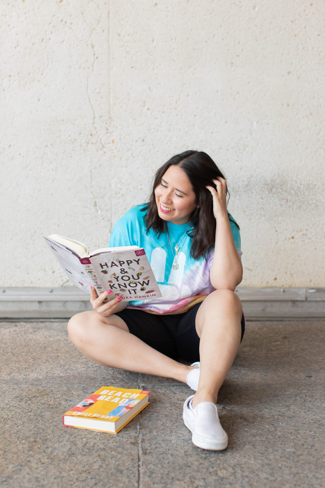 Book Review by popular NYC life and style blog, Live Laugh Linda: image of a woman sitting and reading a book by Laura Hankin and Emily Henry.