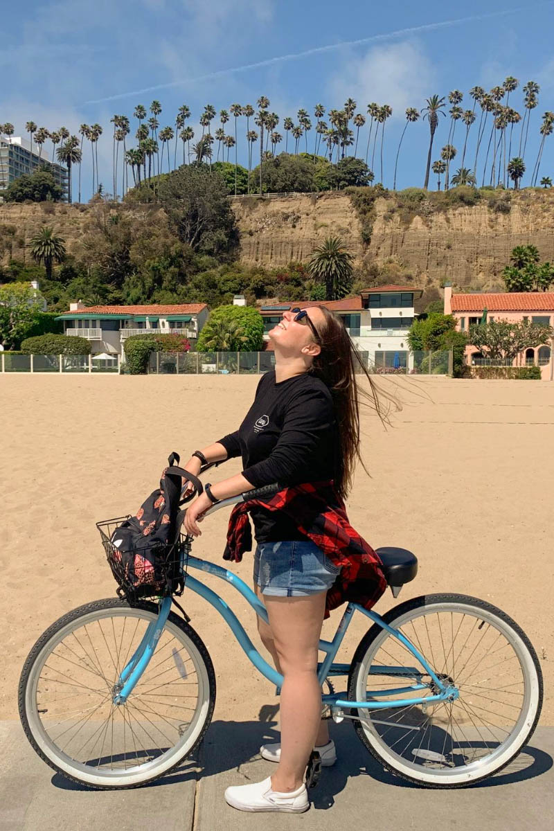 Friends In New York City :: Meet Anna - Senior E-commerce Manager by popular New York lifestyle blog, Live Laugh Linda: image of a woman on a bike on the beach in California.