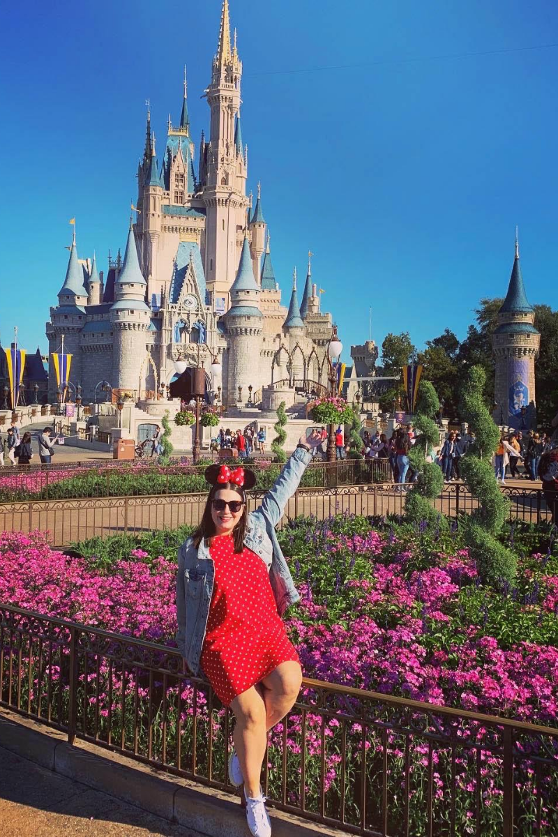Friends In New York City :: Meet Anna - Senior E-commerce Manager by popular New York lifestyle blog, Live Laugh Linda: image of a woman in Walt Disney World in front of the Cinderella Castle in a Minnie red polka dot dress