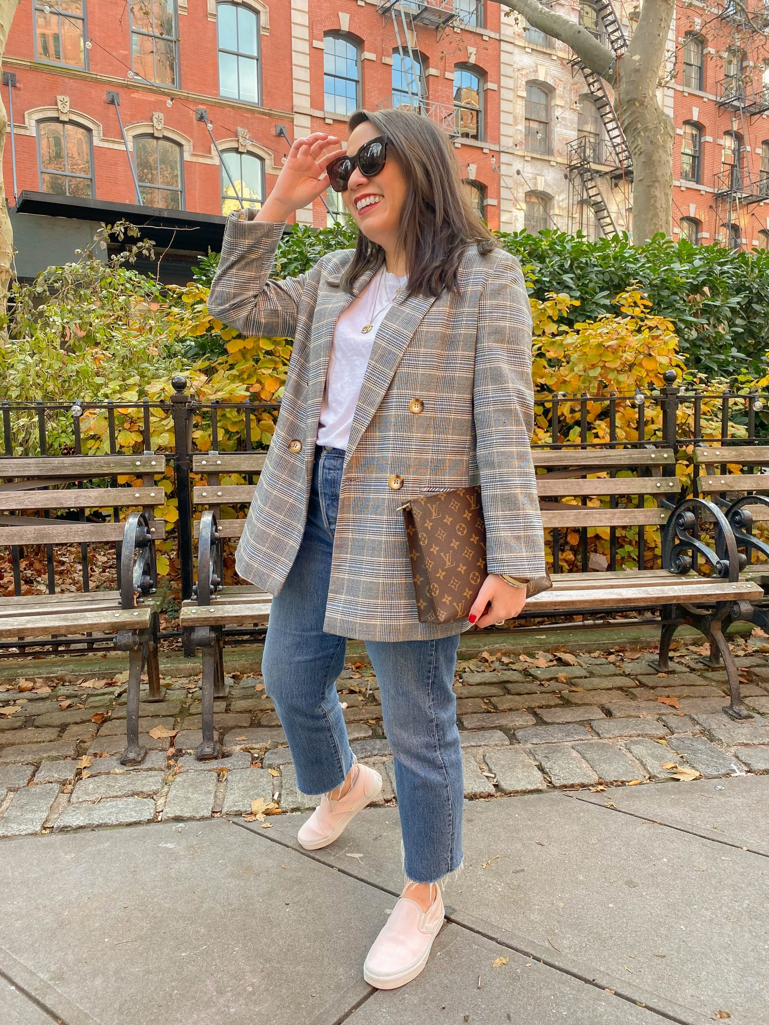 5 Daily Habits to Establish in 2021 by Basically A Mess (image of a woman in NYC with trendy plaid blazer and Louis Vuitton toiletry pouch)